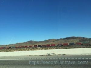 延々と続く荒野の中のコンテナを乗せた列車